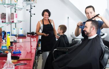 Glad female hairdresser cutting male client