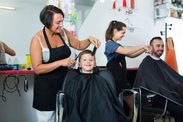 Happy boy sitting in chair and getting hair cut