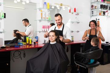 hairdresser cutting hair of female client.