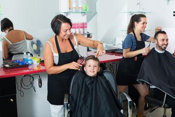 Little boy sitting in chair and getting hair cut