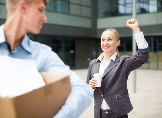 Boss woman is wishing good luck to office worker