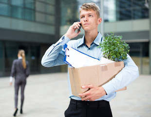 Young businessman with box is talking phone and searching new job