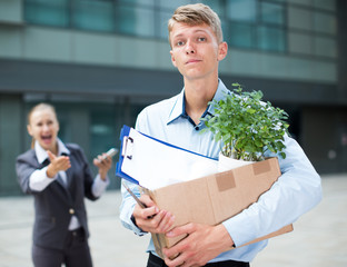 Businessman is standing upset near office with box