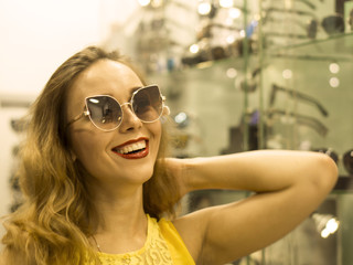 Young Attractive Smiling Girl in Yellow Dress is Measures Sunglasses in the Mall
