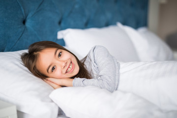 Cute beauty little girl lying in bed at home