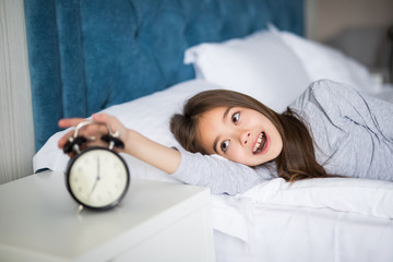 Portrait of shocked cute little girl holding alarm clock and looking at camera while lying in bed in the morning
