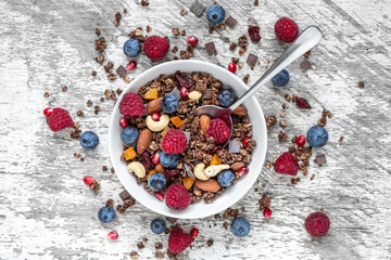 homemade chocolate muesli or granola in a bowl with a spoon, berries, dried fruits and nuts