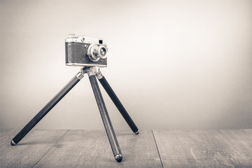 Retro old outdated manual film camera circa 1950s on wooden table. Vintage style sepia photo