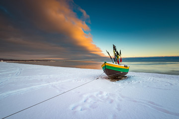 Fishing boat at snow covered beach in Sopot. Winter landscape. Poland. Wall mural
