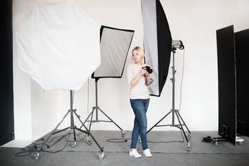 backstage to photoshooting in studio with professional lighting equipment, photographer looking at the pictures from camera display