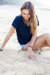 Charming woman sits on white beach and draws heart on sand.
