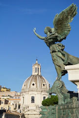 Angel Statue at Monumento Nazionale a Vittorio Emanuele II overlooking the Nome de Maria al Foro Traiano Church at the Trajan Forum in the city of Rome, Italy