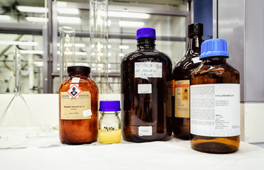 Bottles with chemicals on the desk in laboratory