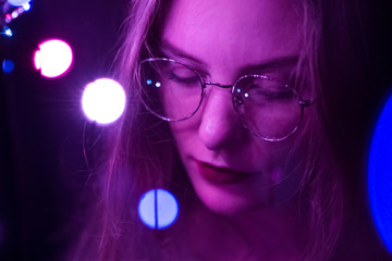 Portrait of a fashion beautiful white girl with glasses in the dark and bokeh Violet tinting. Effect of the focus of the low intensity of sharpness.