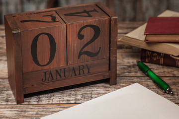 Perpetual Calendar in desk scene with blank diary page, January 2nd