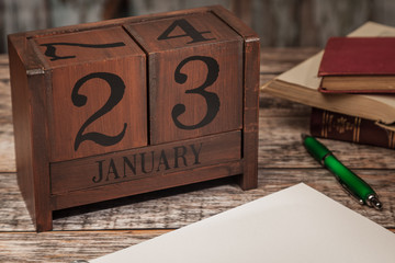 Perpetual Calendar in desk scene with blank diary page, January 23rd