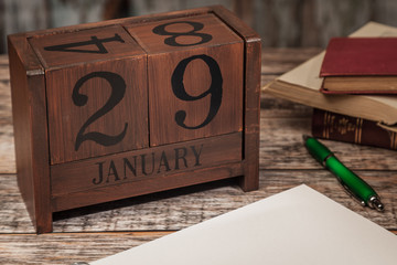 Perpetual Calendar in desk scene with blank diary page, January 29th