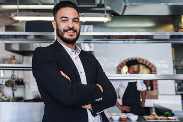 Young businessman standing in his restaurant