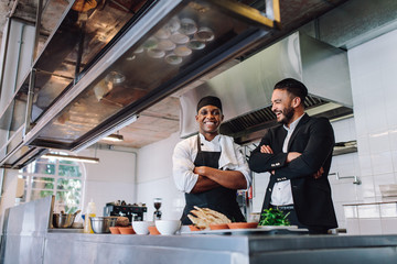 Smiling restaurant owner and chef standing in kitchen