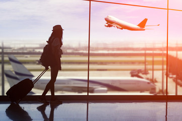 Young woman is standing near window at the airport and watching plane before departure. Wall mural