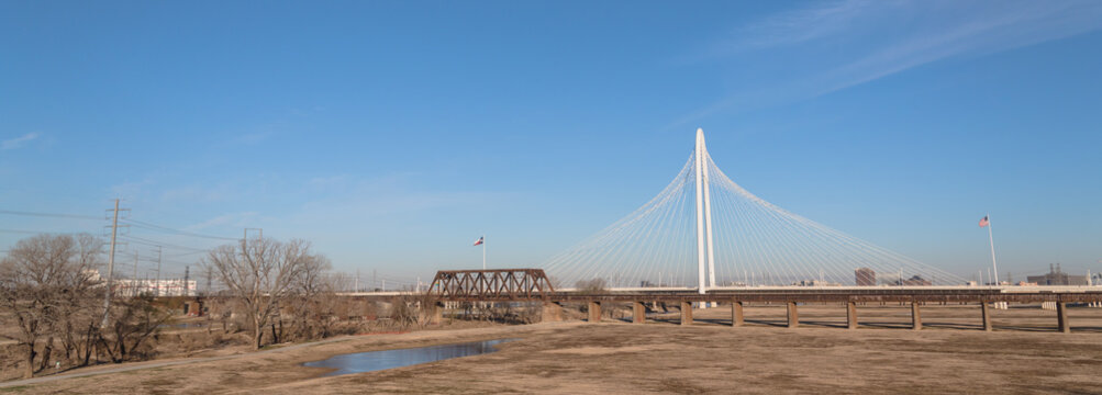 Margaret Hunt Hill and old railway bridge in Downtown Dallas, Texas, USA spans the Trinity River. It is named after an heiress and philanthropist. Transportation and cityscape background. Panorama