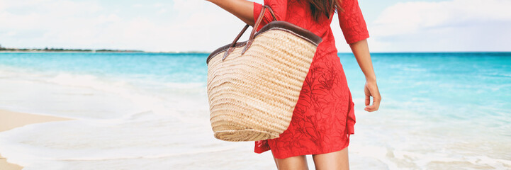 Wall Mural - Beach bag vacation woman walking relaxing on tropical holidays holding tote purse for summer accessories for the beach. Tourist walking with red beachwear dress on travel holidays. Panorama crop.