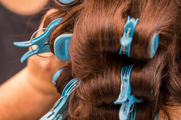 Hairdresser rolling curlers in a womans hair