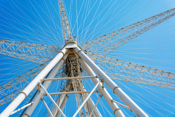 Ferris wheel on cloudy sky background