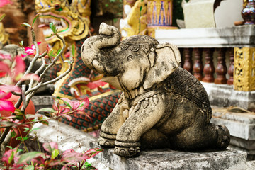 Stone sculpture of elephant near to Thai Buddhist temple. Chiang Mai, Thailand.