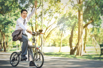 Asian business people use their bicycles to travel to work every morning.
