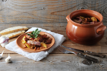 dish cooked in a pot - potatoes, beans, smoked in a clay pot