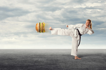 The woman karate kicking the hamburger. The concept of healthy eating.