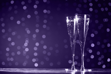 Wall Mural - Two glasses of champagne on dark bokeh background. Ultra violet tone, color of the year 2018