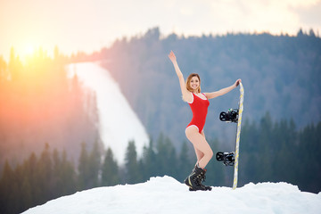 Attractive woman snowboarder wearing red swimsuit, posing with snowboard on snowy slope at winter ski resort. Mountain, forests and ski slope on the background