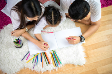Young family drawing together with colorful pencils at home