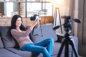 Taking selfies. Cheerful happy young woman sitting on the sofa and taking selfie while holding a camera in front of her