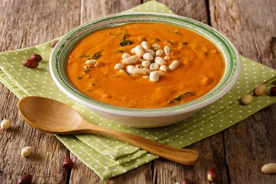 Dietary peanut soup with greens close-up on a plate. horizontal