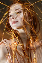 A young girl with red hair and with a luminous garland. Beautiful model with shining bulbs and lights. Gentle makeup. Festive new year's image. Beauty of the face. Photo is taken in the studio.