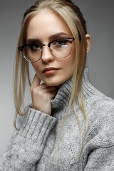 A young blonde girl with straight hair and gentle makeup. Beautiful model in a winter sweater and with glasses. Shining skin. Beauty of the face. Photo is taken in the studio. Cozy image