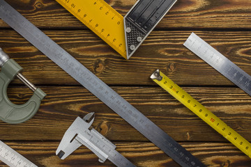 Measuring tools on a wooden background.