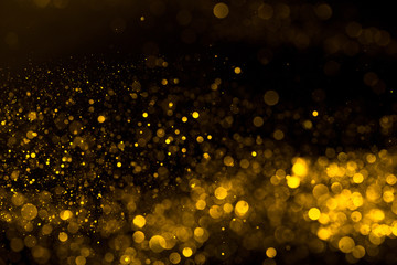 Falling flow of golden glitter dust shiny sparkle bokeh abstract background
