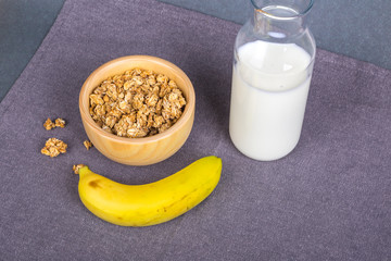 Healthy Breakfast with Muesli Cereal in Bowl and Milk in Bottle and Banana