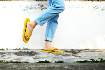 9c674088dc2f Yellow Flip Flops. Female Wearing Sandals and Blue Jeans Standing on ...