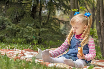 Cute little blonde girl with two ponytails relaxing with a book and a bun in the city park on a spring sunny day.