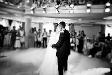 Beautiful wedding couple kissing and danicng in the restaurant during their wedding party. Black and white photo.