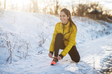 Poster Glisse hiver Young slim athletic girl tying shoelaces in winter sportswear on snowy winter road with earphones in the sunny morning.