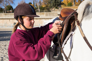 Young girl preparing stirrup on saddle to ride on white horse.
