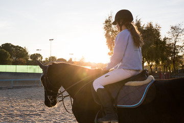 Young teen equestrian girl sitting on back of chestnut horse and riding in backlit.