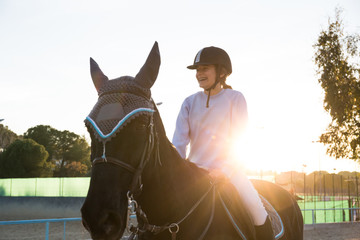 Smiling equestrian girl riding on chestnut equine in sunset backlit.