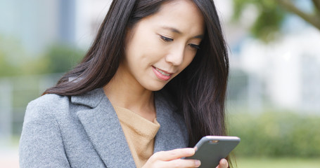 Woman use of mobile phone in park